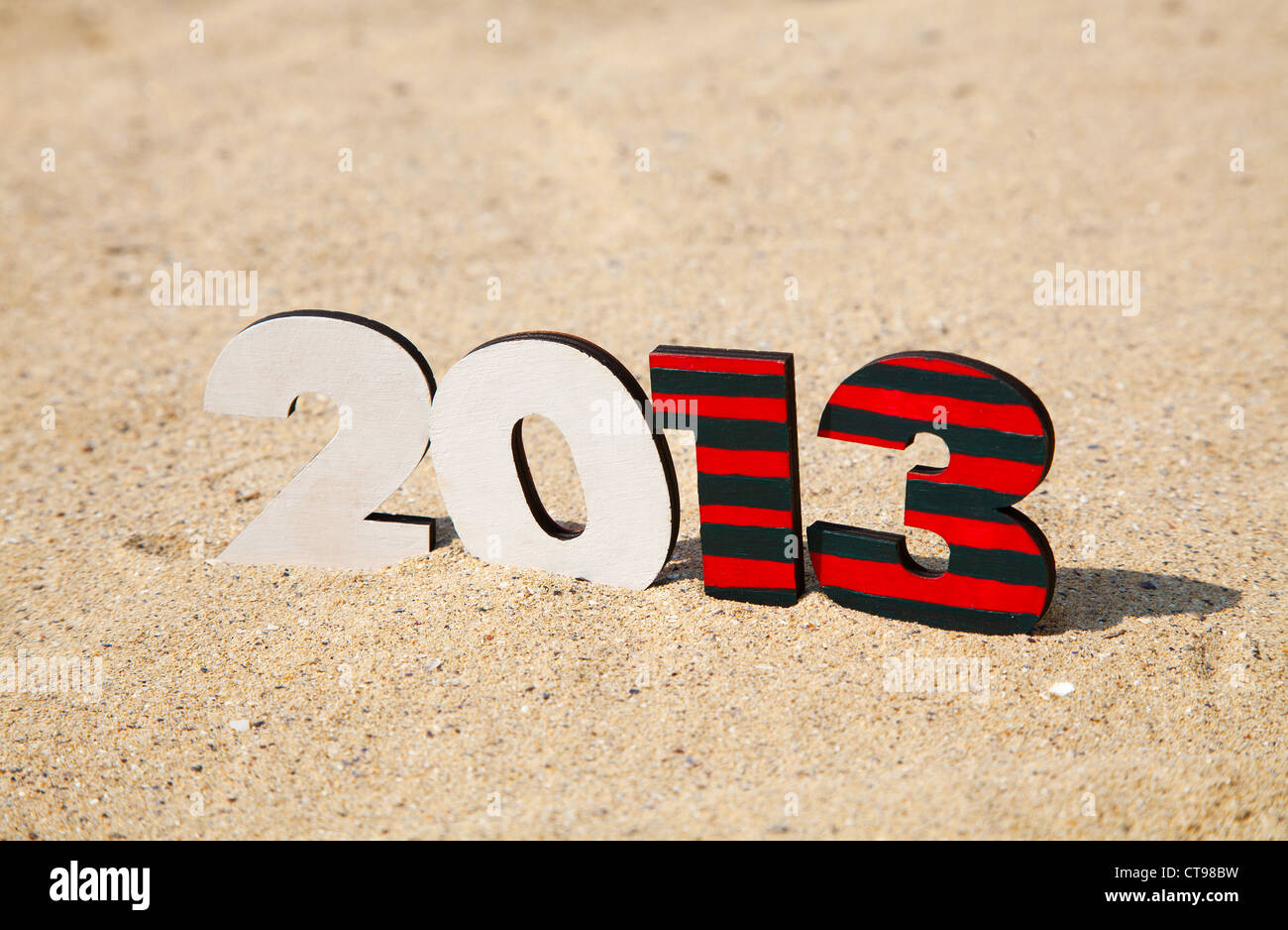 Wooden 2013 year number on the sand at a beach - Stock Image