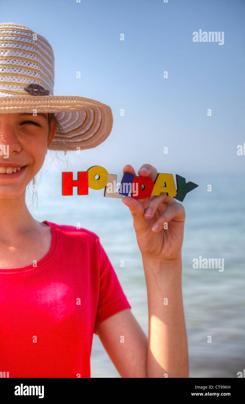 Teen girl at a beach holding word 'Holiday' - Stock Image