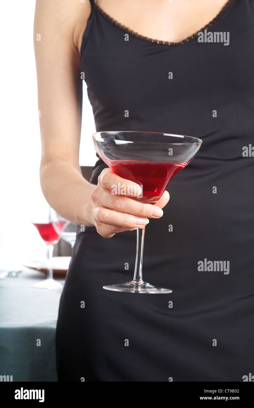 detail of woman hand with cocktail glass red beverage - Stock Image