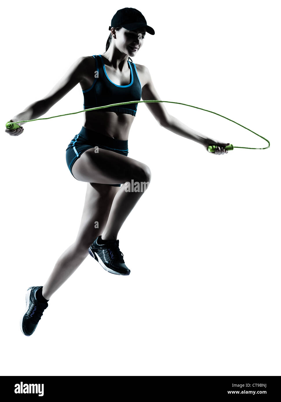 one caucasian woman runner jogger jumping rope in silhouette studio isolated on white background - Stock Image