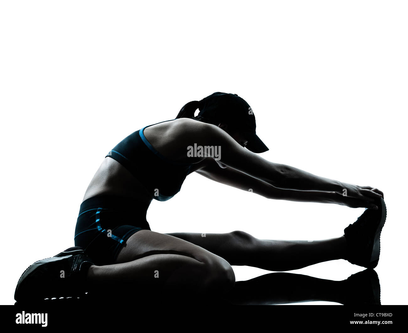 one caucasian woman runner jogger stretching legs warming up in silhouette studio isolated on white background - Stock Image