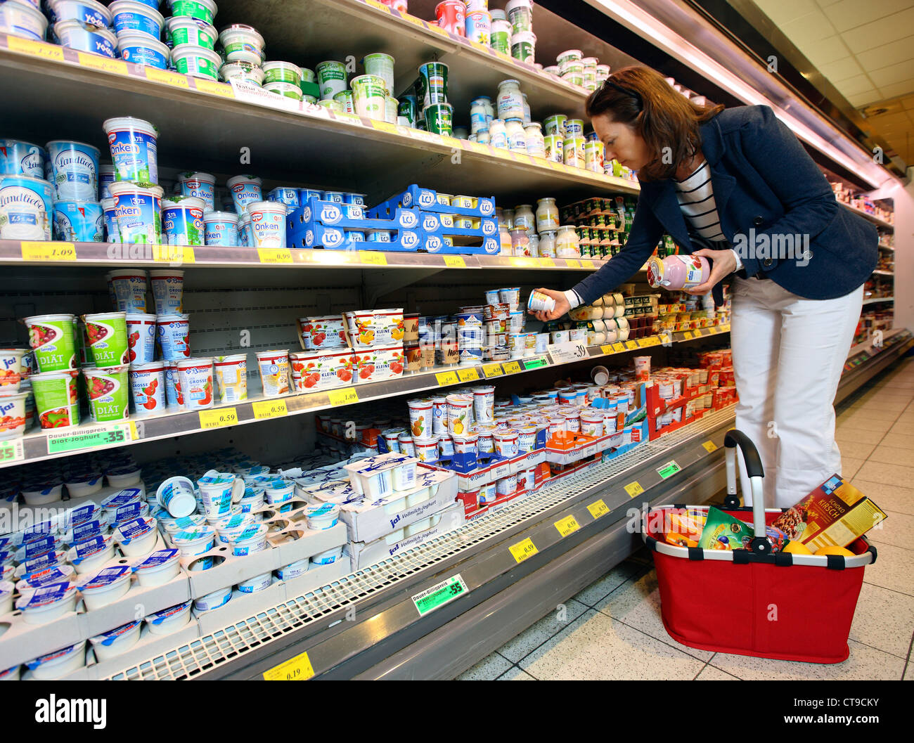 Woman is shopping in a large supermarket. Different products in a refrigerator. - Stock Image