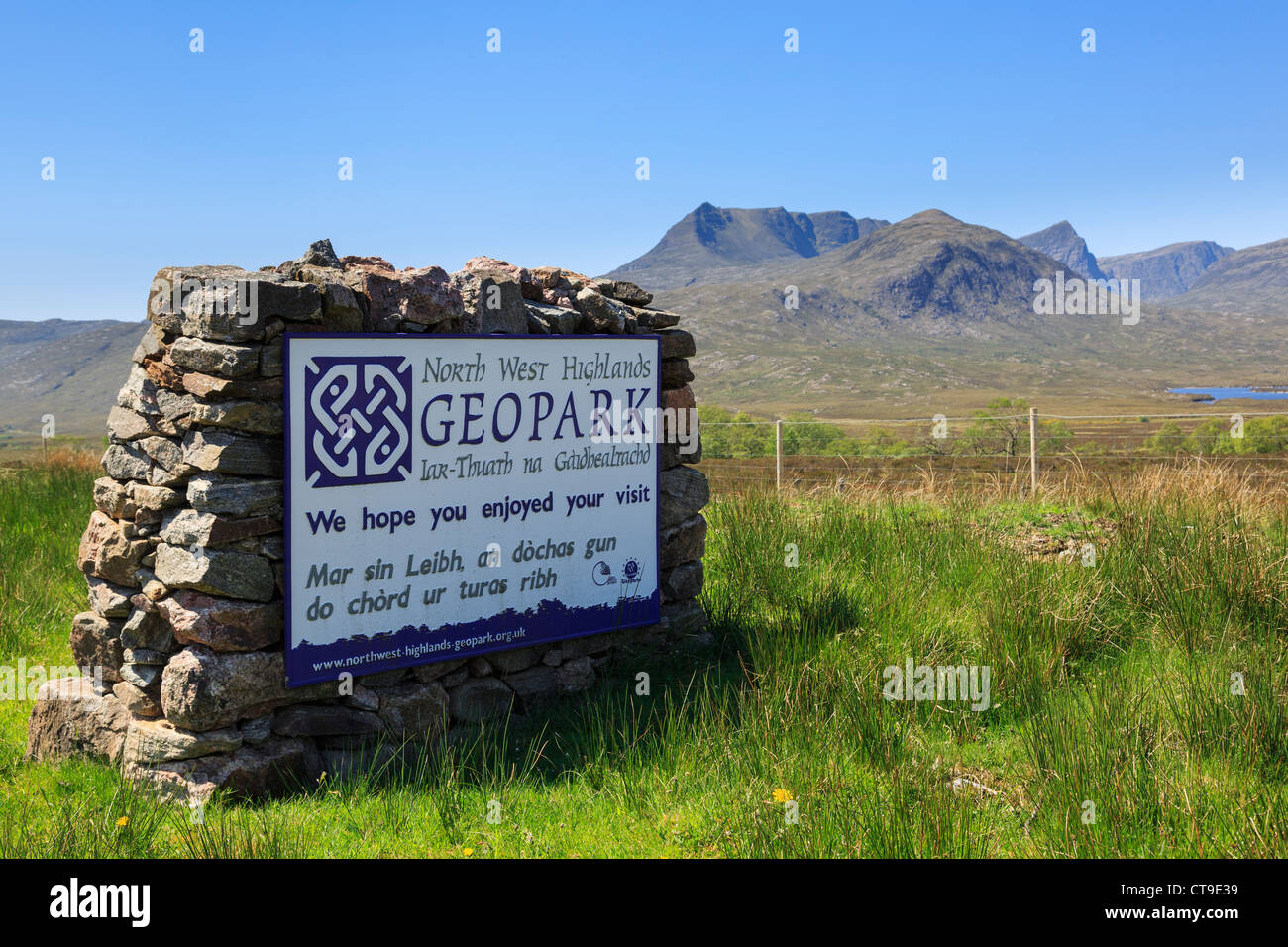 North West Highlands Geopark Gaelic bilingual sign with Ben More Coigach mountain beyond. Assynt, Ross and Cromarty, - Stock Image