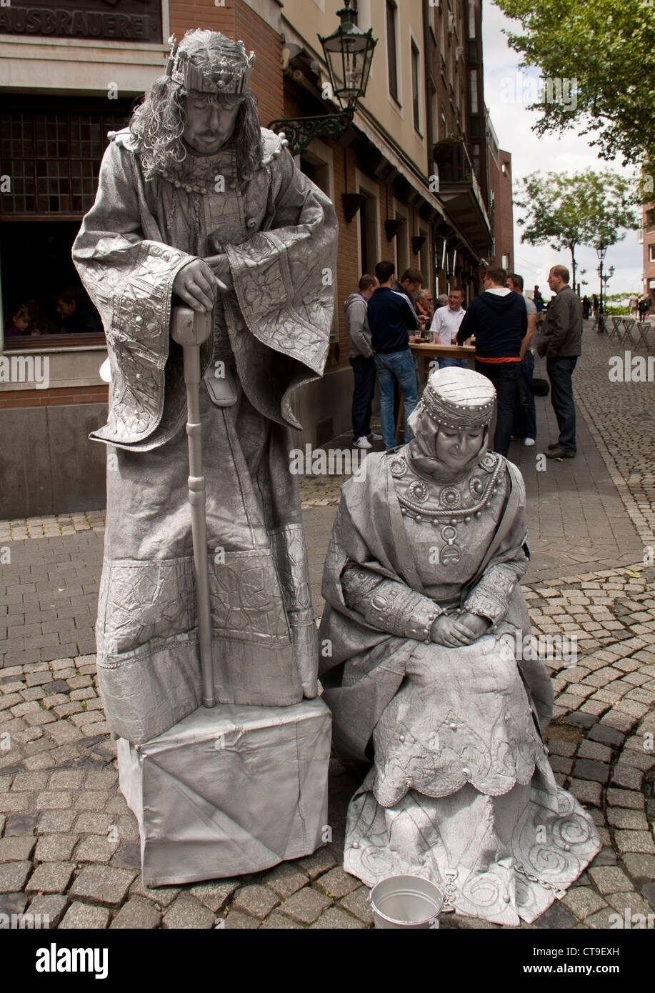 Dusseldorf, Germany - June 9th 2012. Street artists dressed as king and queen, bow to the people crossing by. - Stock Image
