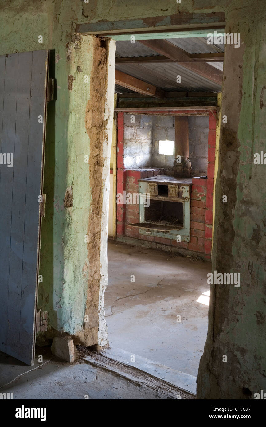 Looking through a doorway to an old oven nside an abandoned and derelict farmhouse in the Western Australian outback. - Stock Image