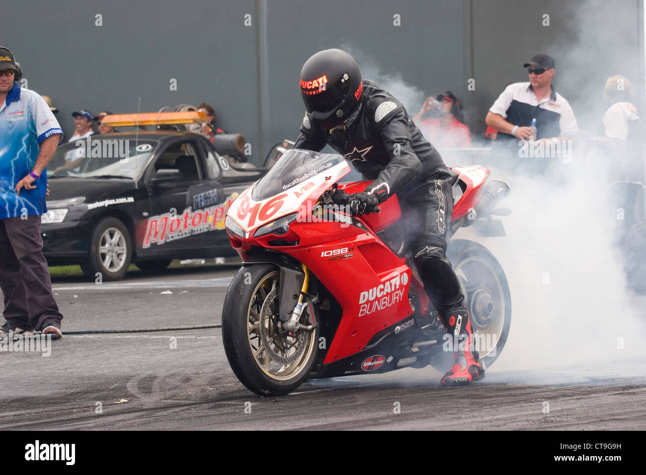 Ducati 1098R mounted drag racer performing a burnout to heat up the rear tyre before racing on the quarter mile. - Stock Image