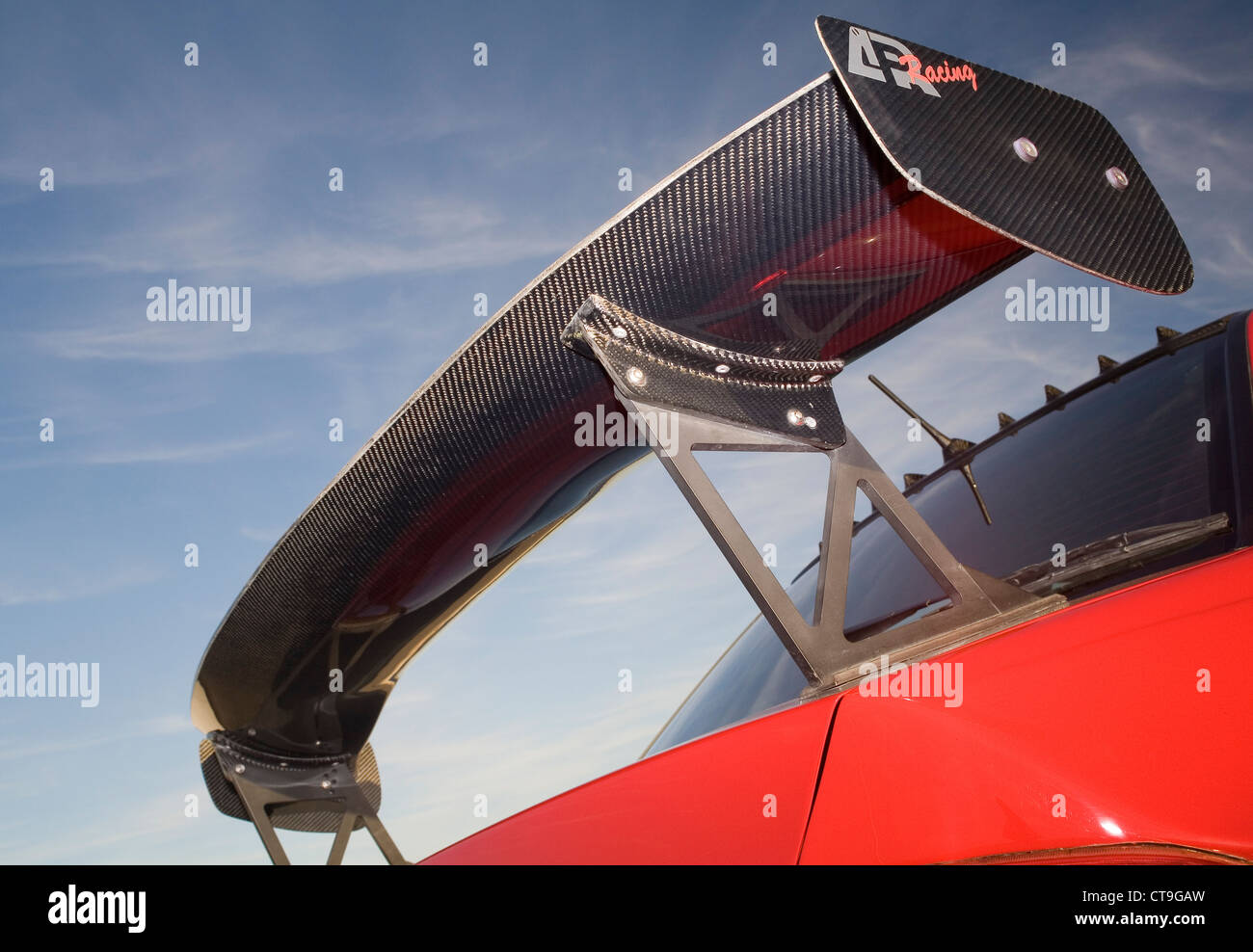 Massive huge aerodynamic carbon fibre wing bolted to the rear of a modified custom boy racer style sports car. - Stock Image