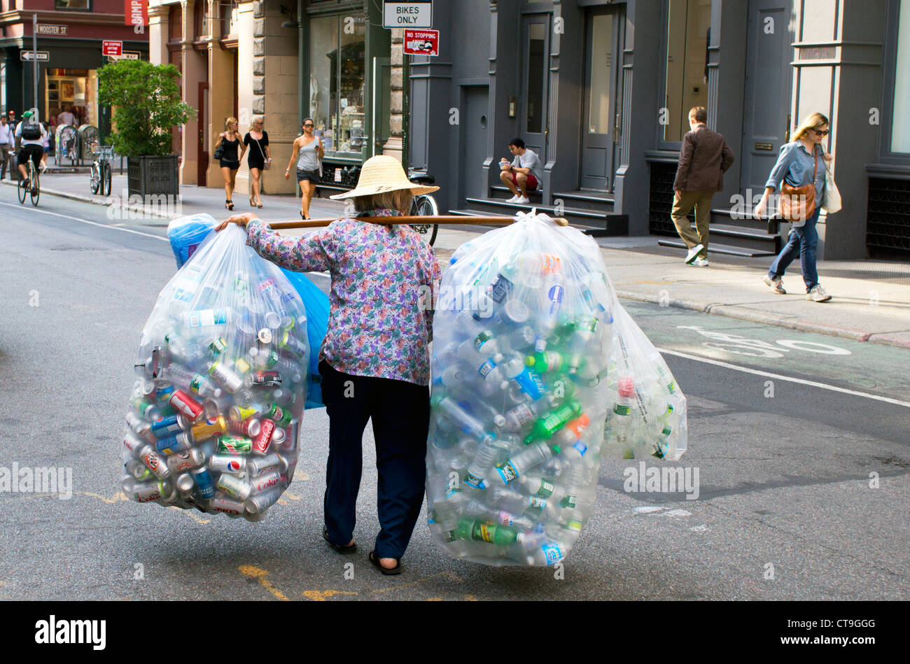Elderly Asian woman collecting cans and bottles for the deposit to recycle in New York City - Stock Image