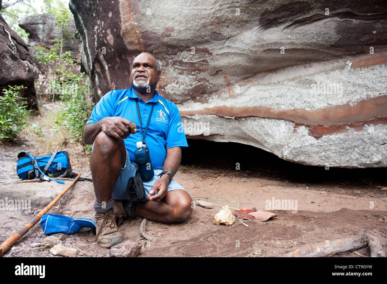 Nugal-warra elder Wilfred Willie Gordon of Guurrbi tours explains indigenous rock art cave painting on Aborginal - Stock Image
