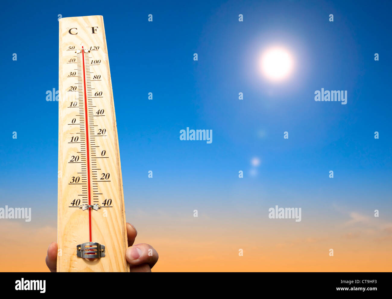 hand holding thermometer and heat weather - Stock Image
