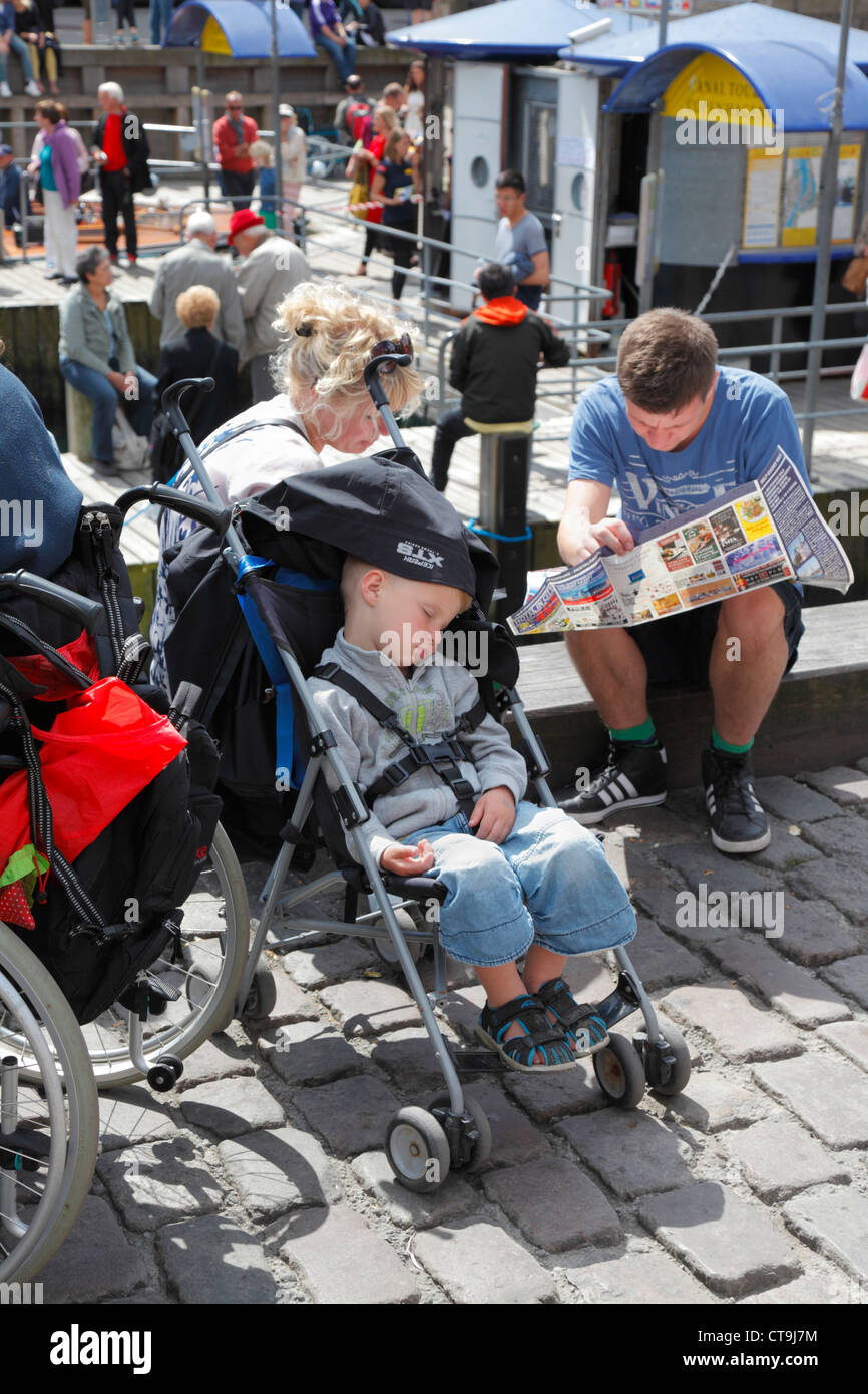 Young boy taking a nap in his stroller on crowded Nyhavn quayside while his parents are checking the city map of - Stock Image