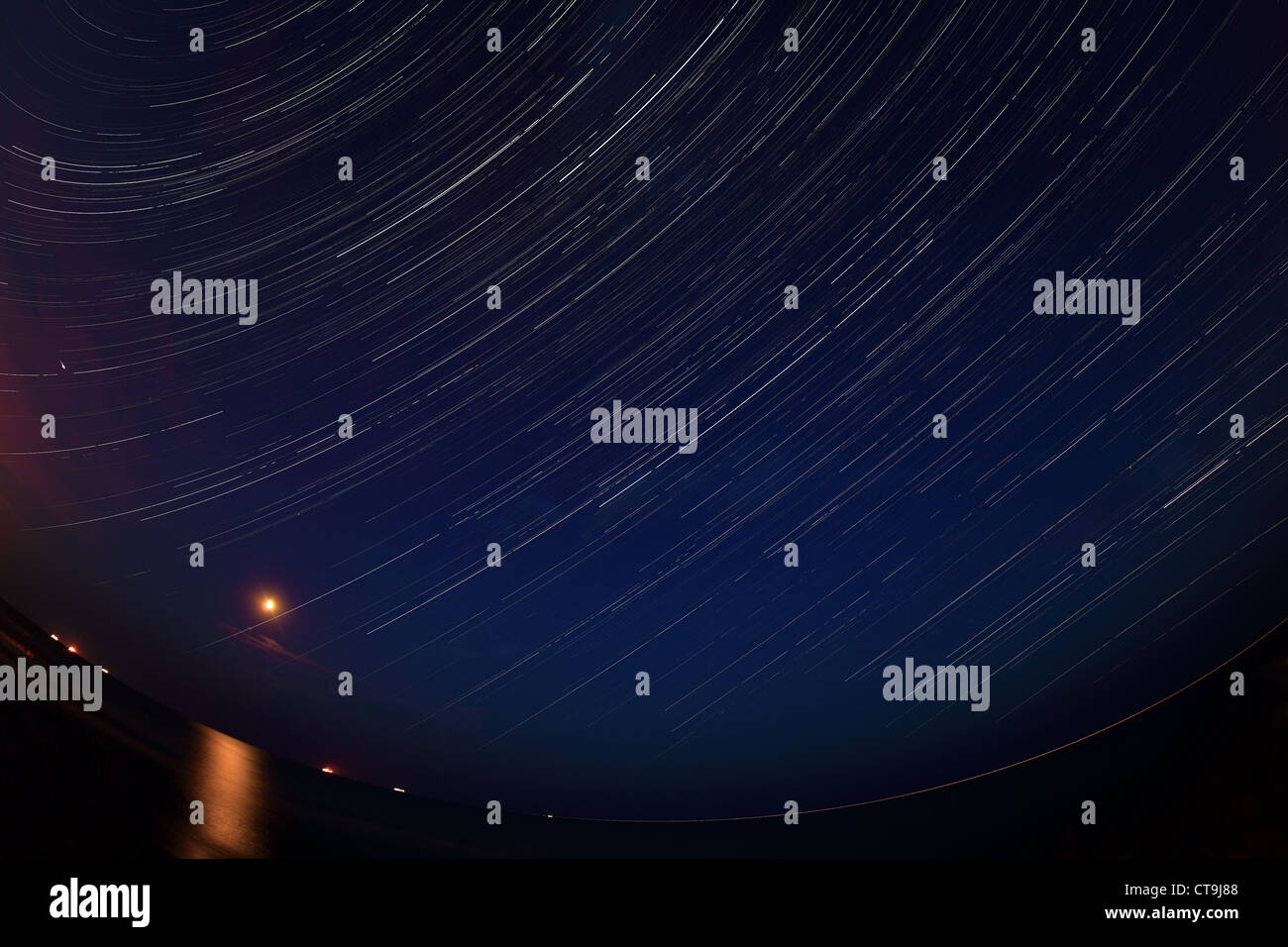 Night landscape, night sky with moving stars over the sea. Moon - Stock Image