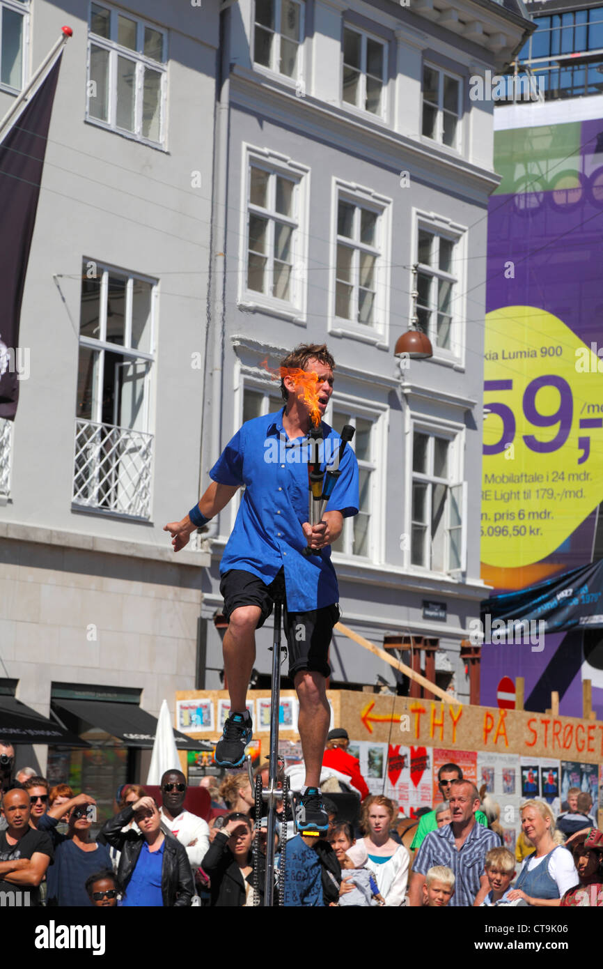 Popular artist  juggling with fire on one-wheel bike on the pedestrian, shopping and entertainment street Stroeget - Stock Image