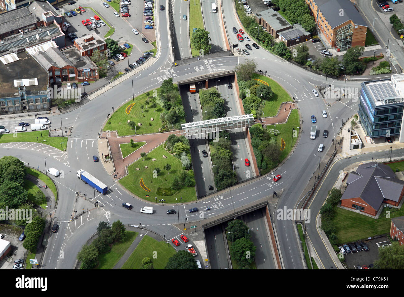 aerial view of a large roundabout over a dual carriageway road with greenery and a footbridge - Stock Image