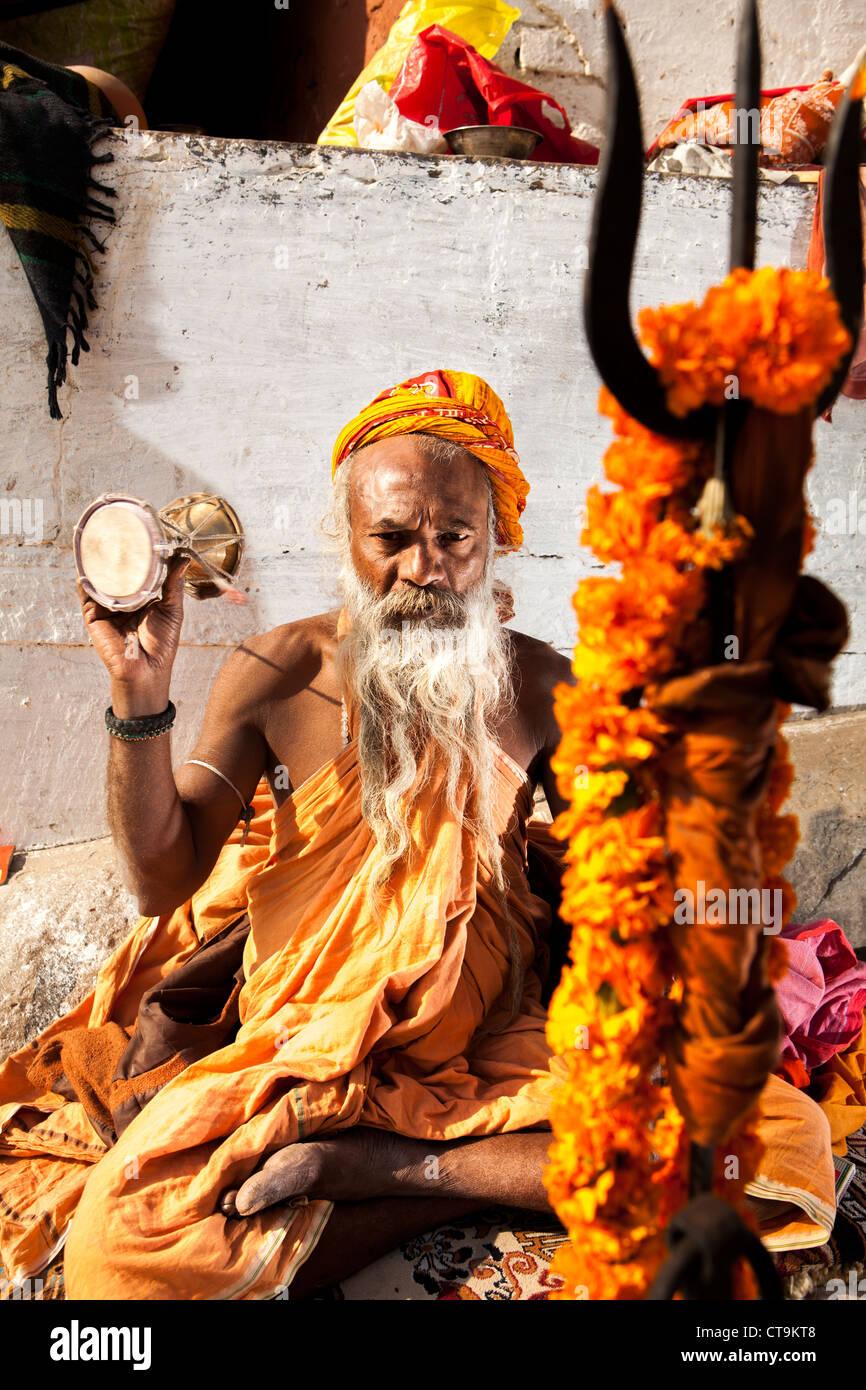 Hindu monk Sadhu pray in front of his trident , Varanasi, Uttar Pradesh, India - Stock Image
