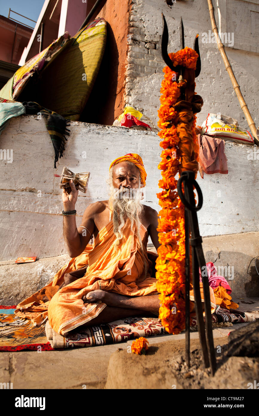 Hindu monk Sadhu pray in front of his trident , Varanasi, Uttar Pradesh, India - Stock Image