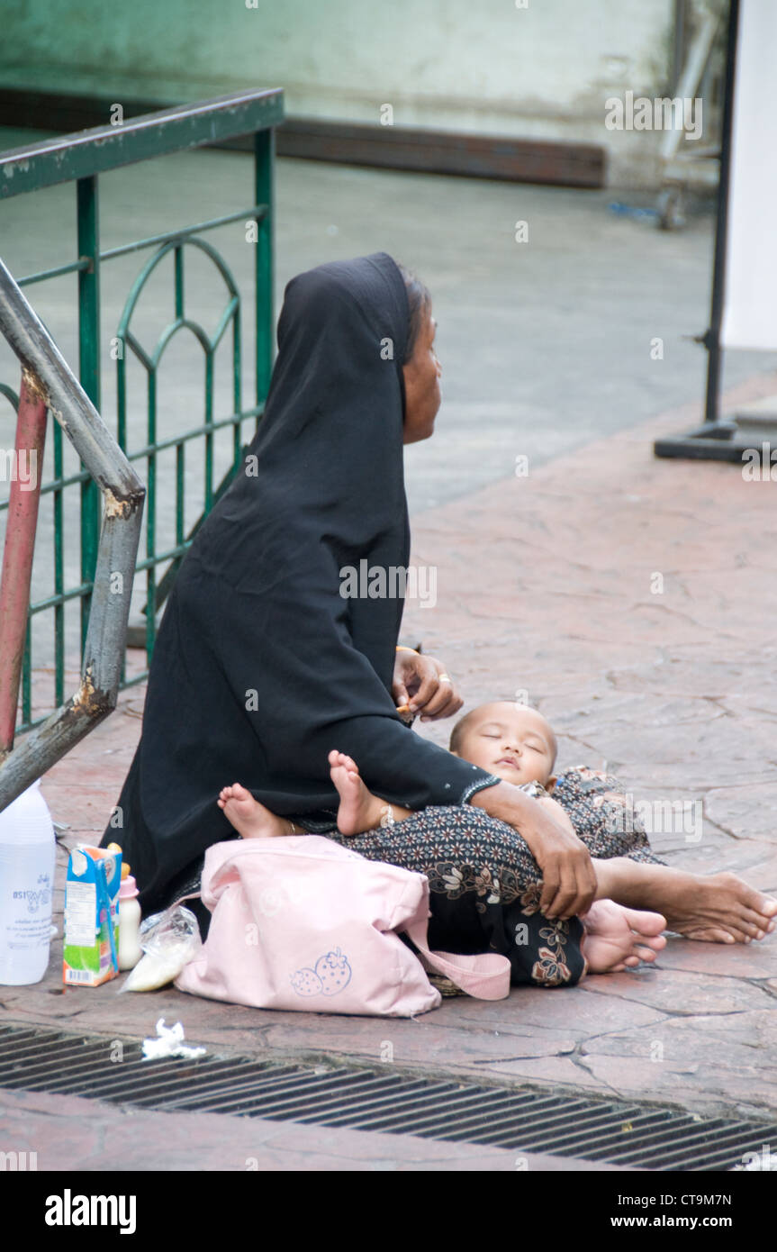 A woman and her baby begging in Bangkok, Thailand - Stock Image