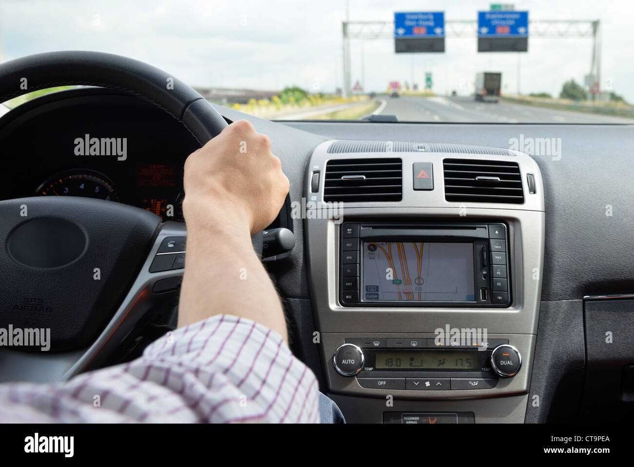 Hand on the steering wheel of a modern, luxurious car, taking an exit on a motorway - Stock Image