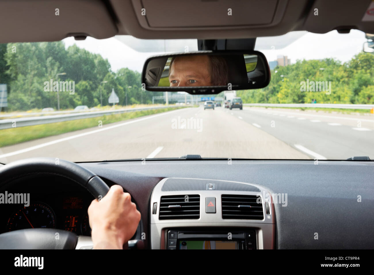 Man, driving a car, with his eyes reflected in the rear view mirror - Stock Image