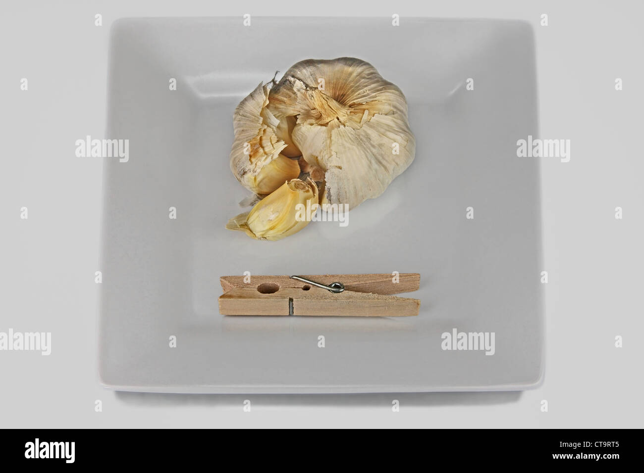 a square dish with cloves of garlic and a clothespin. The clothespin clamp is to hold your nose - Stock Image