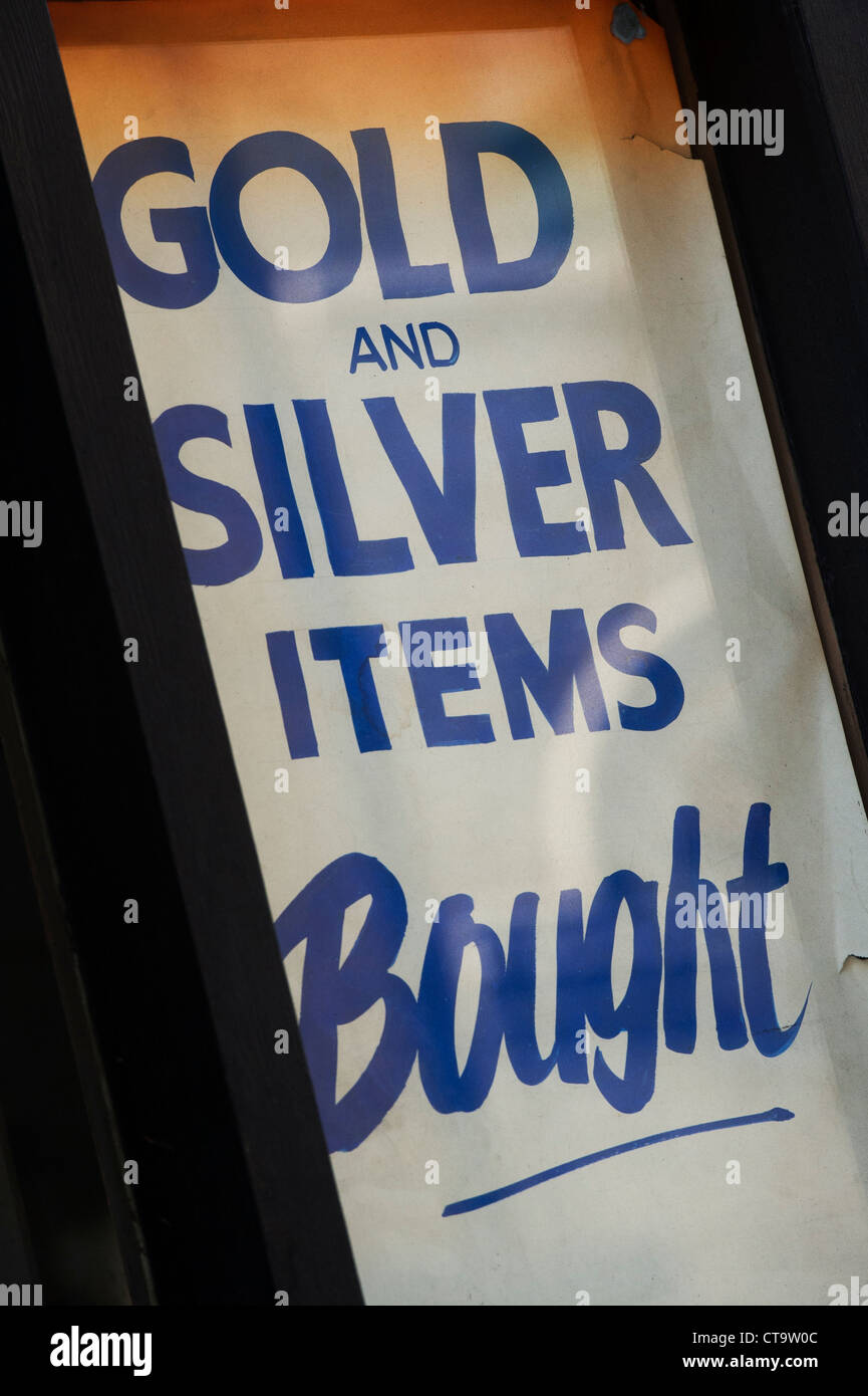 Gold and Silver items bought poster in a shop window. London, England - Stock Image