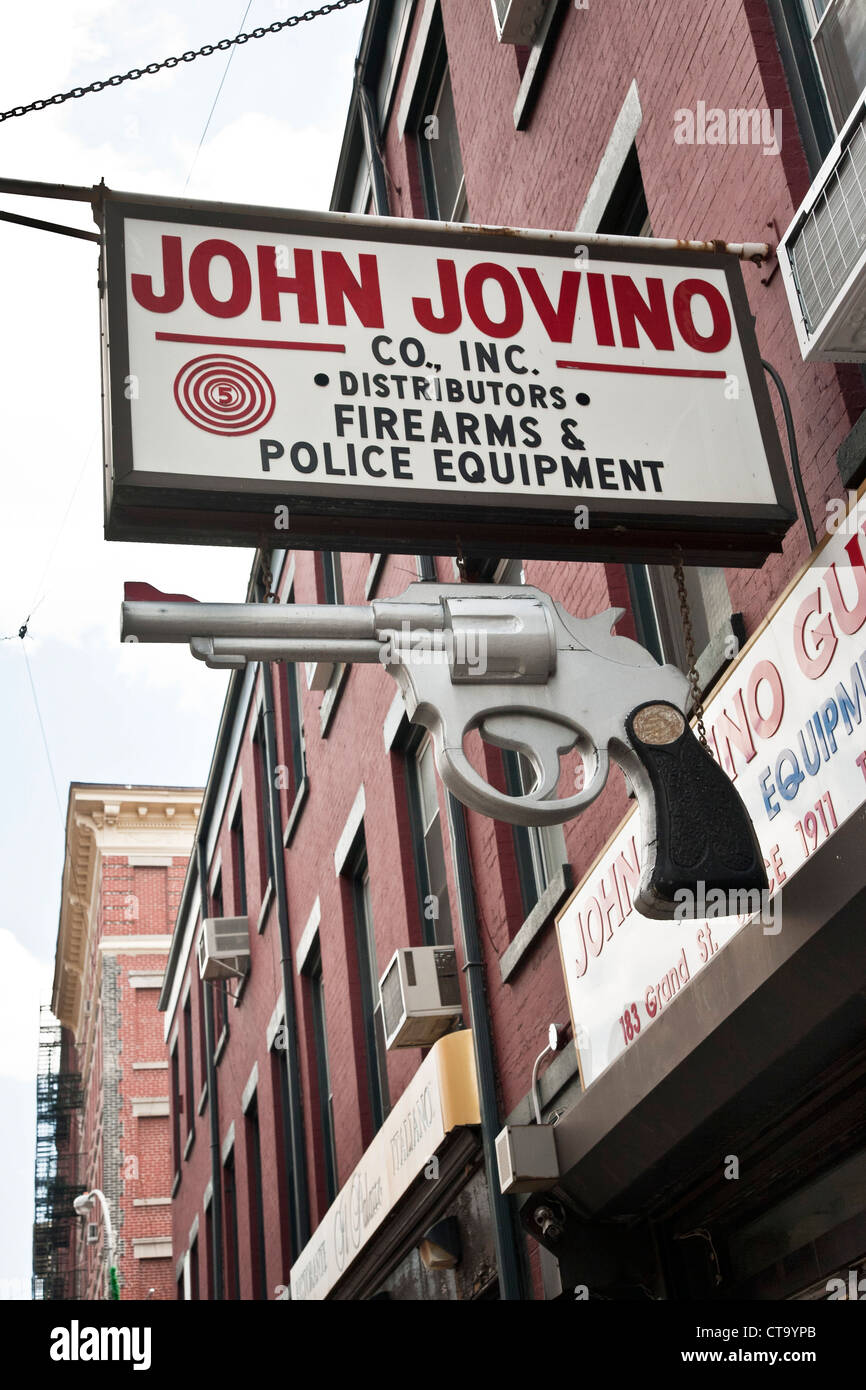gun shop sign with realistic oversize carved revolver hanging under it on Grand street in Little Italy New York - Stock Image