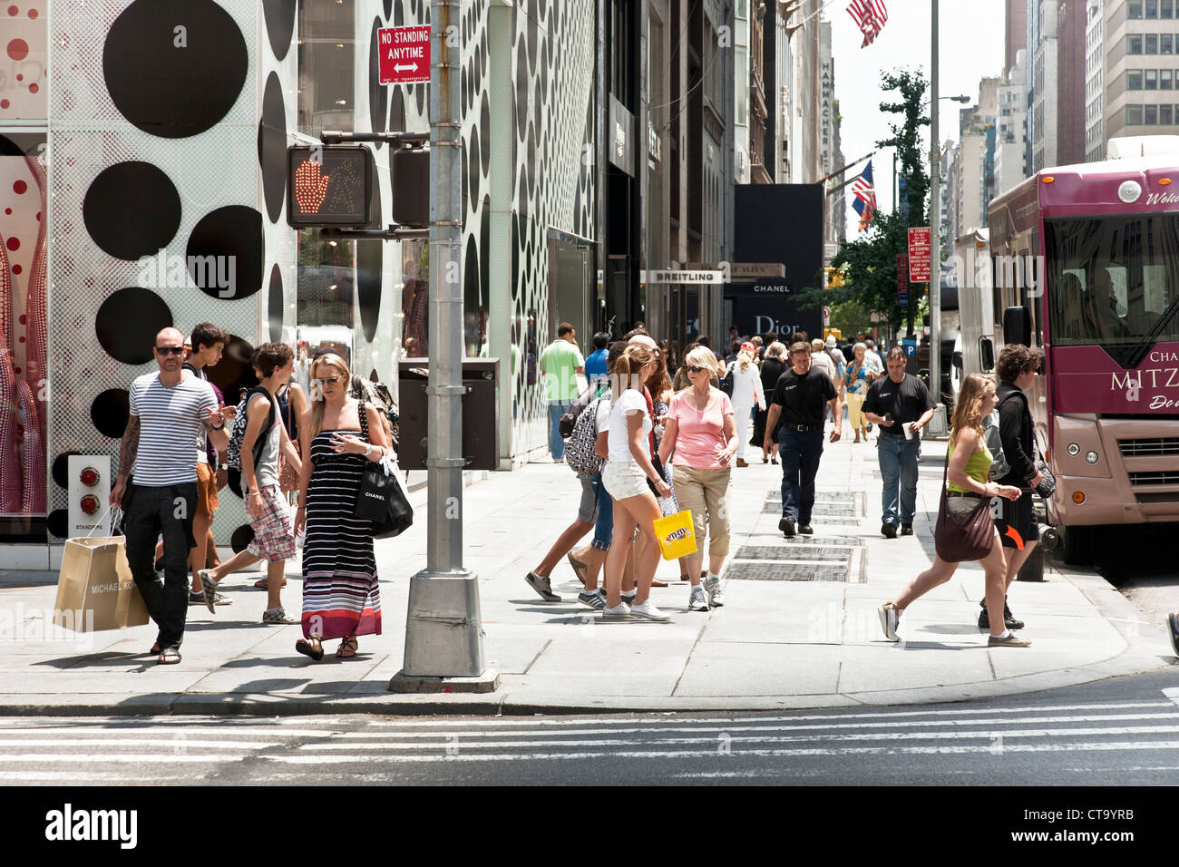shoppers & pedestrians crowd corner of 5th Avenue & 57th street on hot summer day in midtown Manhattan New - Stock Image