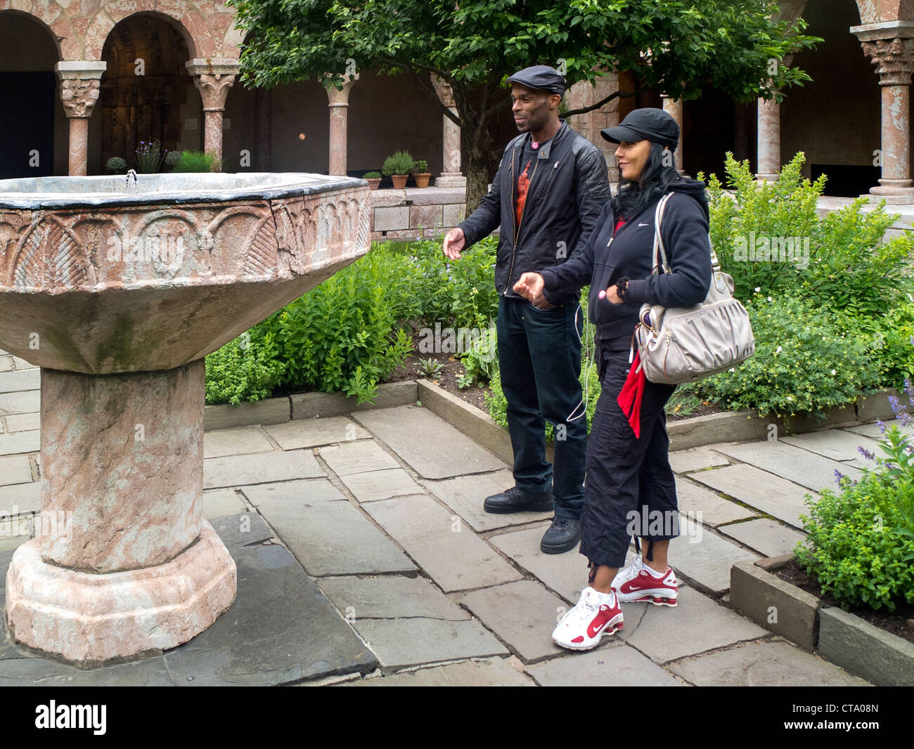 An African-American couple make a wish as they toss a penny in a medieval fountain at The Cloisters Museum in New - Stock Image