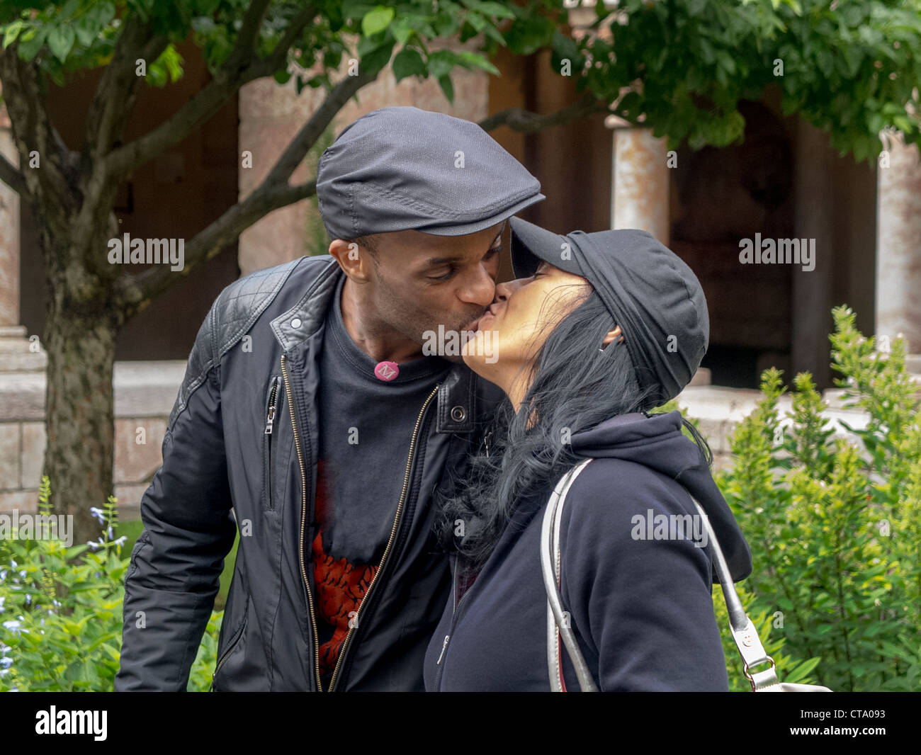 African-American couple kiss for good luck after making a wish at a medieval fountain at The Cloisters Museum in - Stock Image