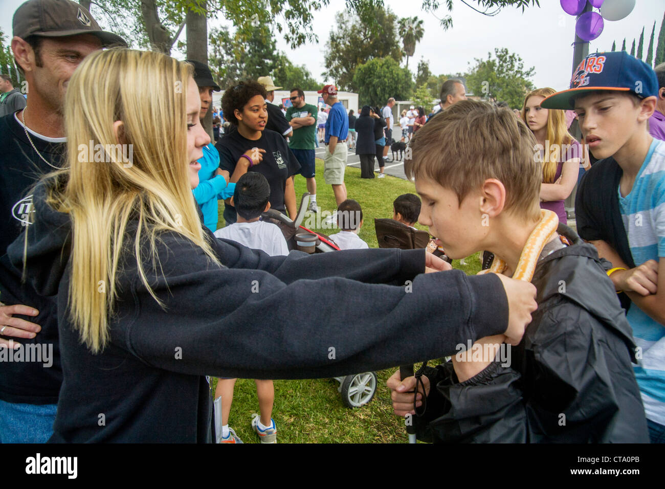 A girl puts a snake around the neck of blind boy to give a tactile experience at a fund raiser for children with - Stock Image