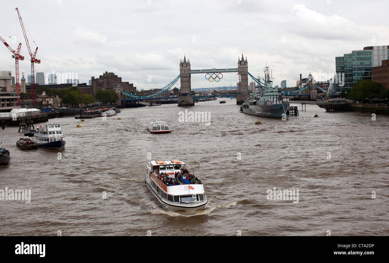 A tourist boat cruises on the Thames River near the London Bridge. London will host the Summer Olympics beginning - Stock Image