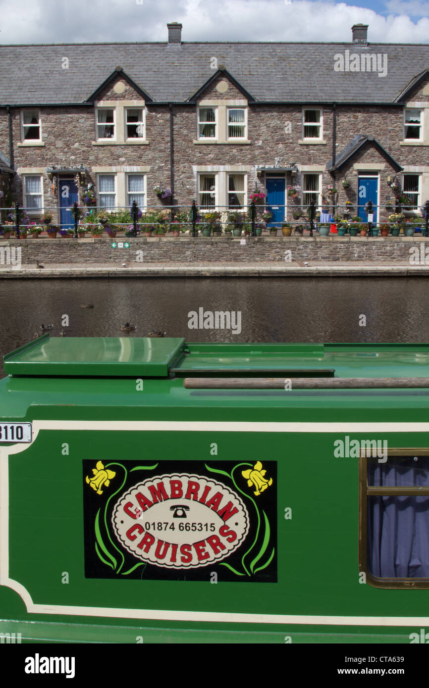 Cambrian Cruisers narrowboat Sian at the Brecon and Radnor Canal with quaint cottages in the background - Stock Image