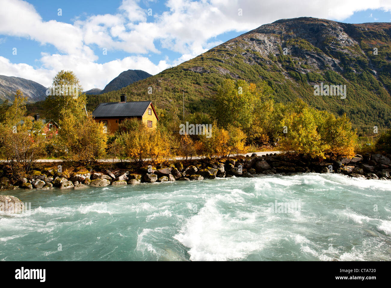 Tourquoise coloured river in front of a wooden house, Autumn, Trail to Nigardsbreen, Jostedalsbreen, Jostedalen, - Stock Image