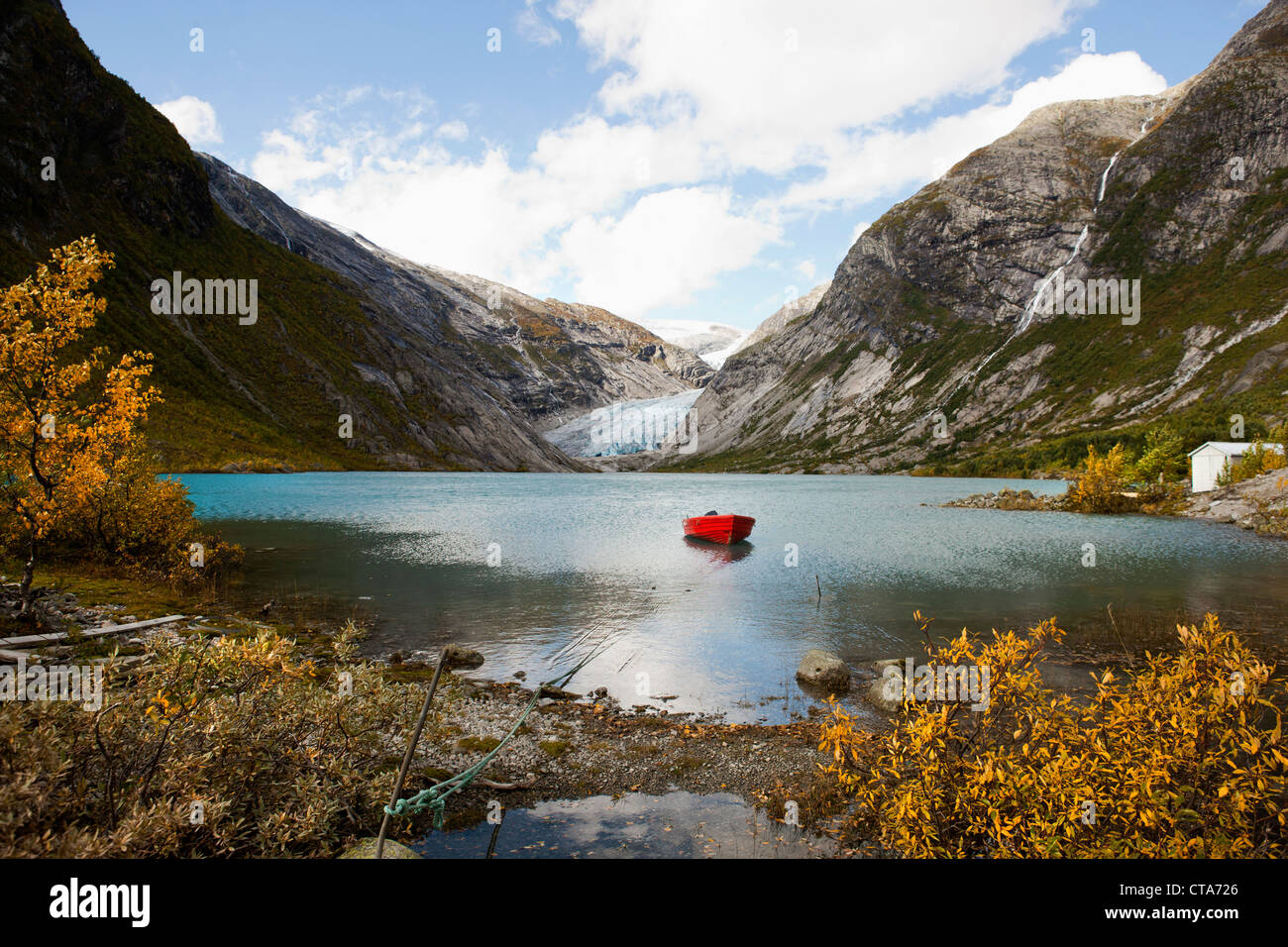 View of Nigardsbreen, red boat on a lake in front of the glacier snout, Autumn, Nigardsbreen, Jostedalsbreen national - Stock Image