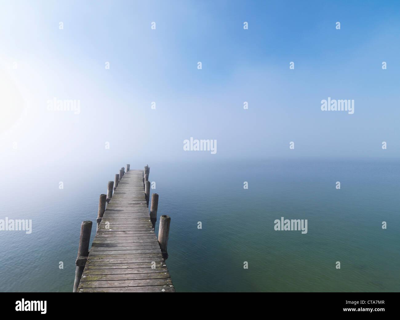 Wooden jetty in fog at lake Chiemsee, Frauenchiemsee, Chiemgau, Bavaria, Germany Stock Photo