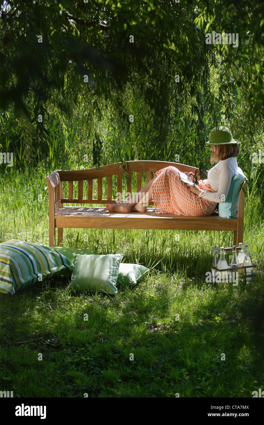 Woman sitting on a garden bench, Simssee, Bavaria, Germany - Stock Image