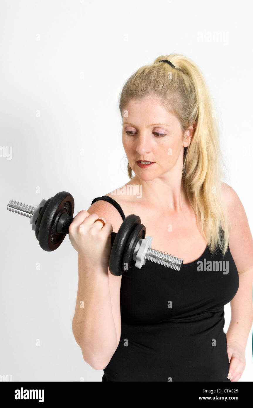 Attractive young Caucasian woman lifting weights using dumbbell against a white background - Stock Image