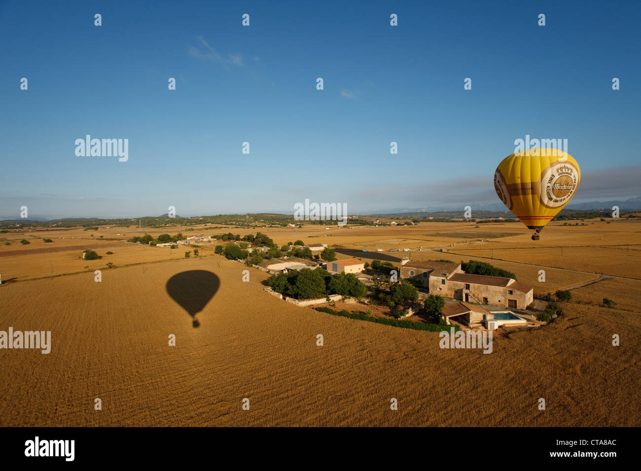 Hot air balloon flying over fields and a farm, plain Es Pla, Mallorca, Balearic Islands, Spain, Europe Stock Photo