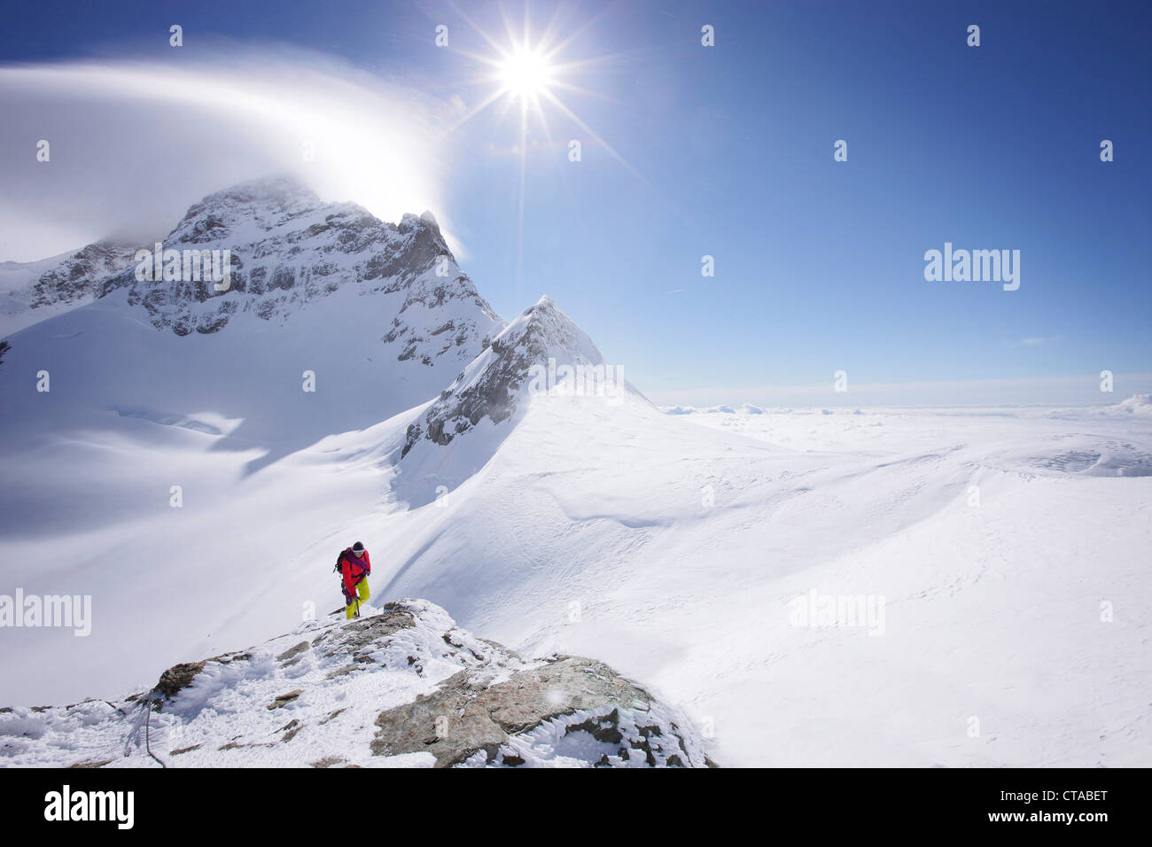 Mountaineer at the summit of Jungfraujoch, Jungfrau in the background, Grindelwald, Bernese Oberland, Switzerland - Stock Image