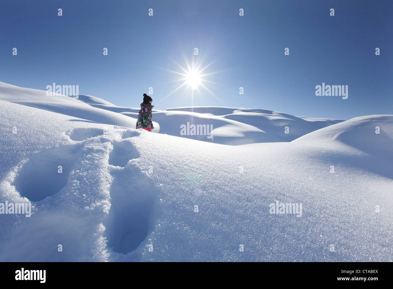 Young girl trudging through deep snow, Kloesterle, Arlberg, Tyrol, Austria - Stock Image