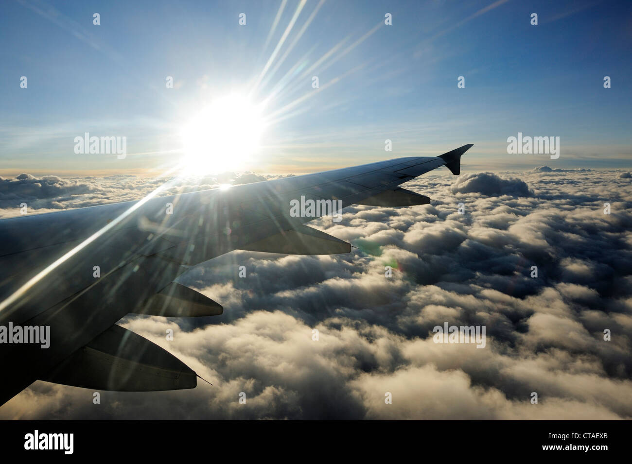 Sun above clouds with wing of airplane, flight from Delhi to Leh, Ladakh, Jammu and Kashmir, India - Stock Image