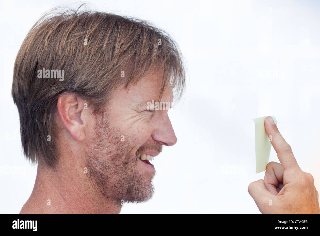 Middle aged man with beard growth looking at yellow note stuck to his finger. - Stock Image