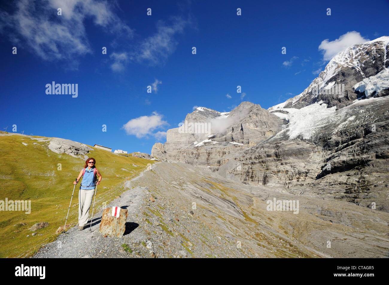 Woman descending, Eiger and Moench in background, UNESCO World Heritage Site Jungfrau-Aletsch protected area, Bernese - Stock Image