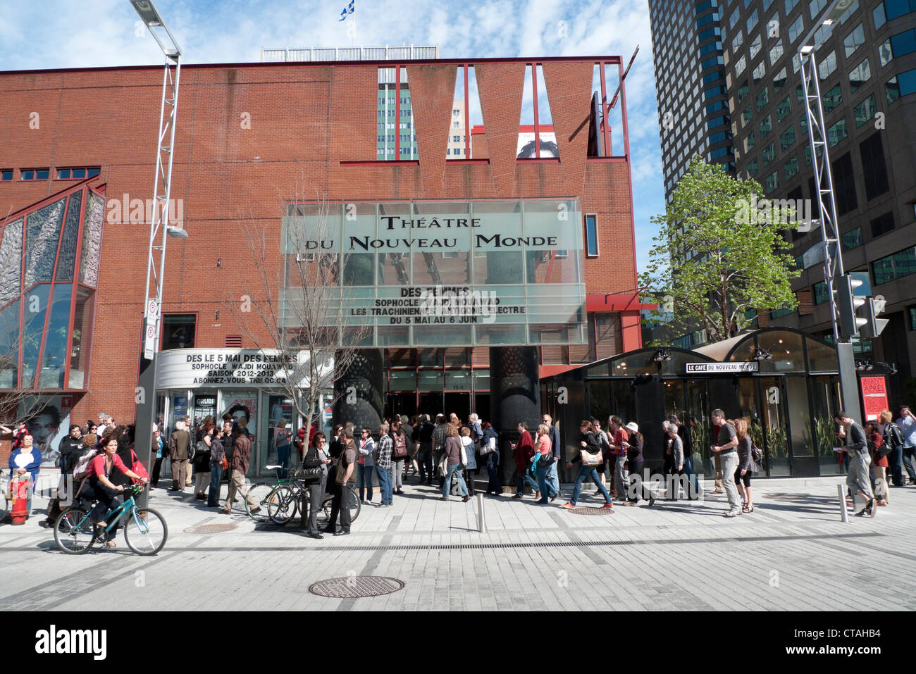 People in the street in a queue outside the entrance of the Theatre du Noveau Monde building in the city of Montreal - Stock Image