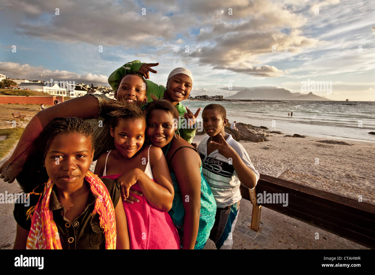 Beach impression with young coloured teenagers at Bloubergstrand, Cape Town, Western Cape, South Africa, RSA, Africa - Stock Image