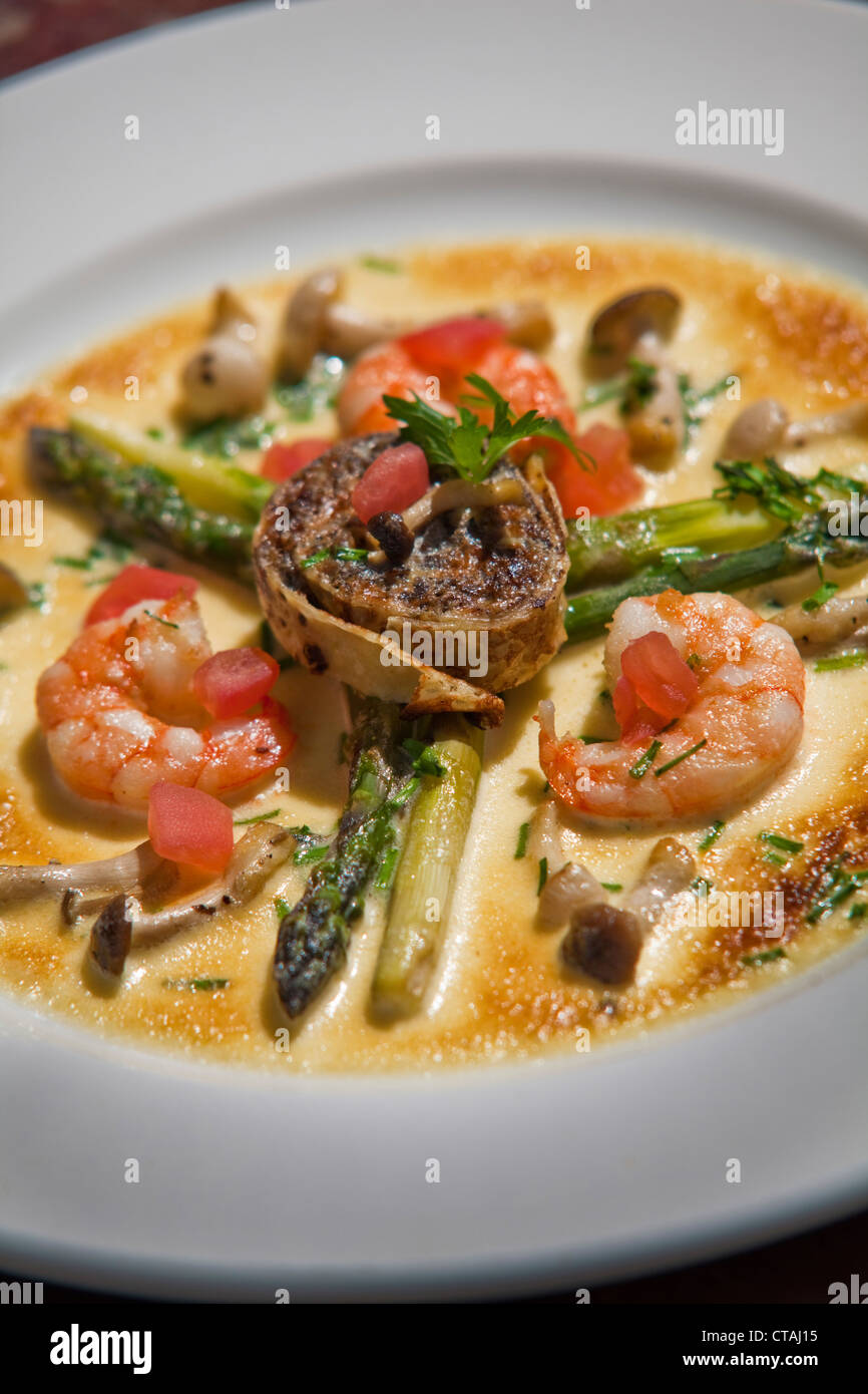 Green asparagus and fresh fried Japanese mushrooms, served with a duxelle roulade, and gratinated in a fontina and - Stock Image