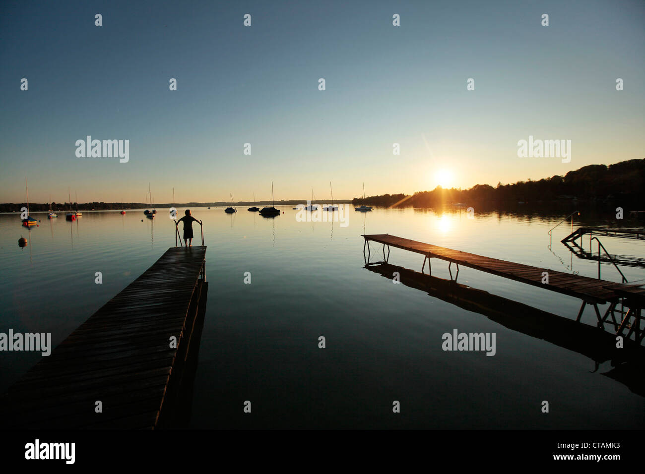 Child on a wooden jetty at sunset, Lake Woerthsee, Starnberg, Upper Bavaria, Bavaria, Germany - Stock Image