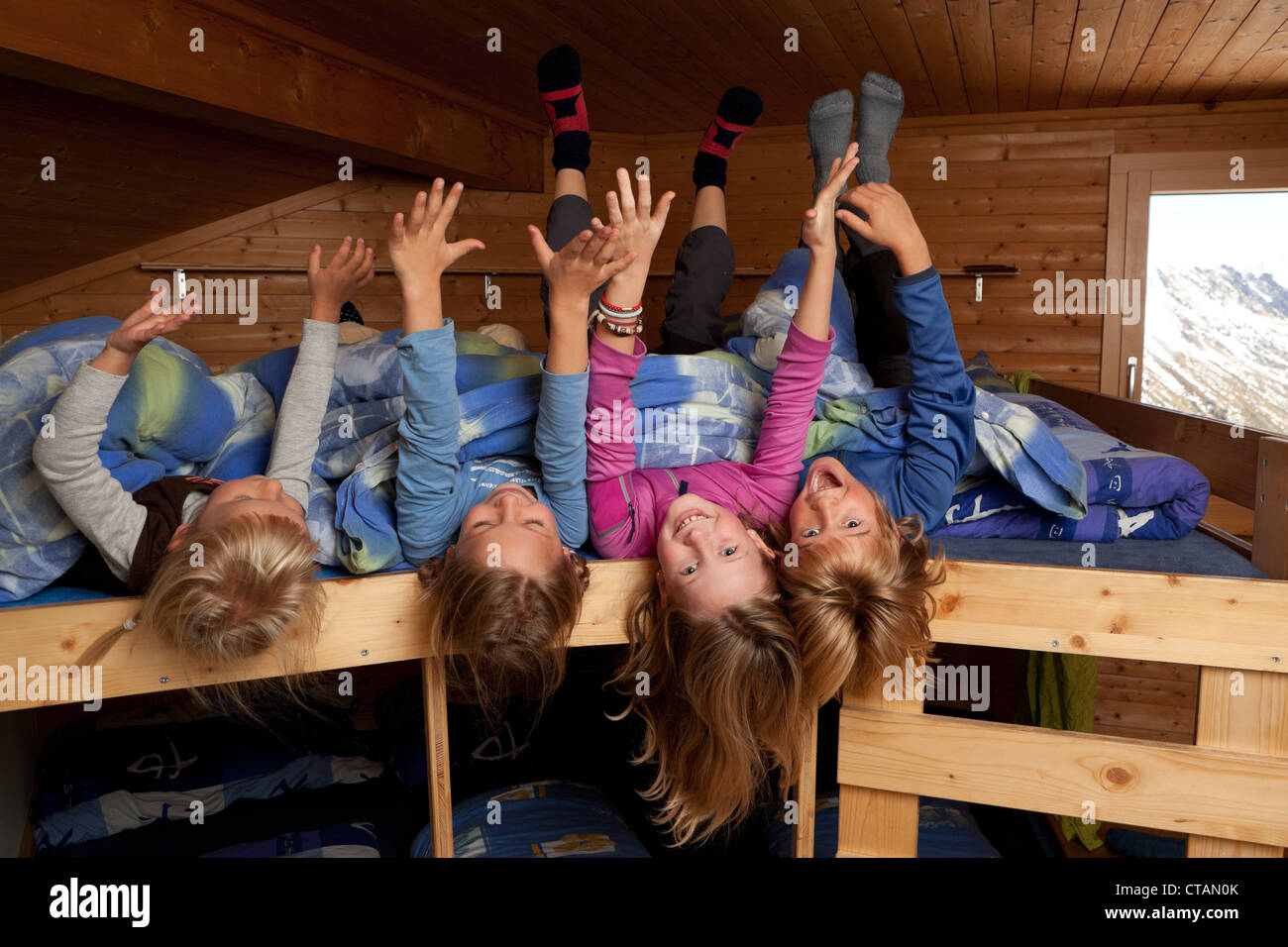 Children, three girls and a boy in a dormitory of a mountain hut, the Sewenhut, Swiss Alpine-Club, kanton Uri, Switzerland - Stock Image
