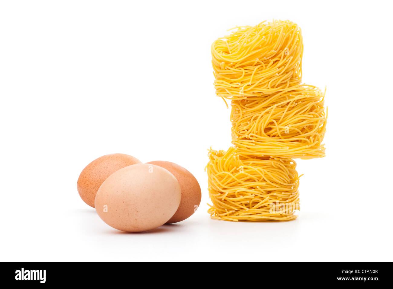 Fresh unprepared noodles and eggs - Stock Image