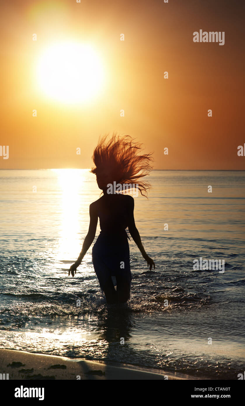 Silhouette of the woman with long hairs running in the sea during golden sunset. Natural darkness and colors. Vertical - Stock Image